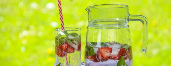 A pitcher of strawberry lemonade on a hot summer day